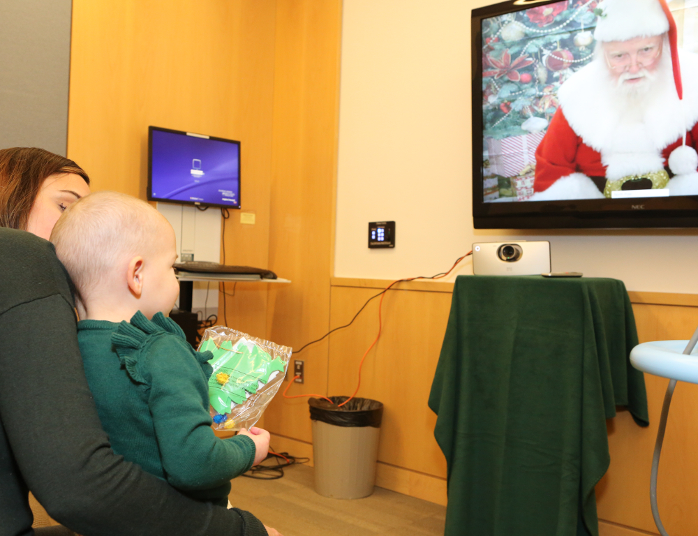 A young girl sits in her mom's lap. The girl looks up at a TV screen bearing an image of Santa Claus.