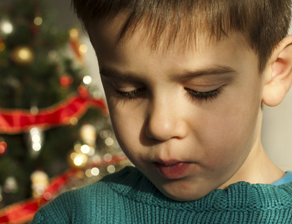A close-up of a young boy in a green sweater, looking downward. A Christmas tree is in the background, slightly out of focus.