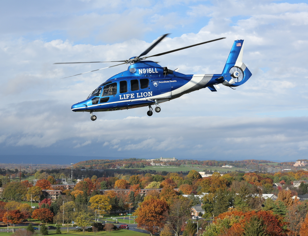 An aerial shot of a Life Lion helicopter above the Hershey skyline. Trees are seen below.