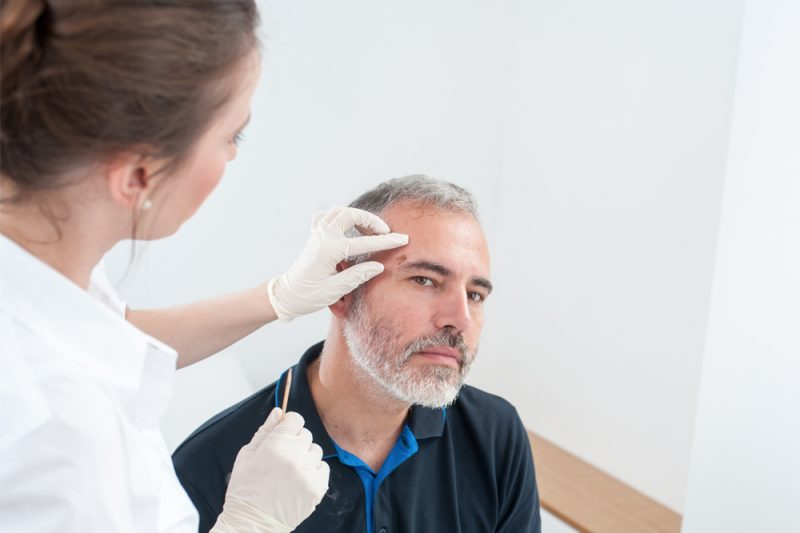 A medical provider in a white shirt and wearing white rubber gloves inspects a growth on a male patient's forehead.