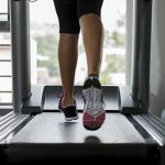 A runner's legs on a treadmill. The runner is wearing sneakers.