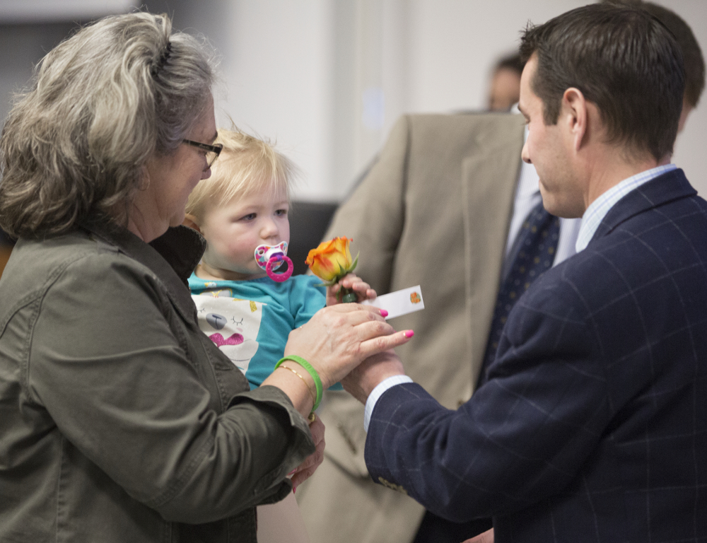 A man hands an orange and yellow rose to a woman who's holding a young child.
