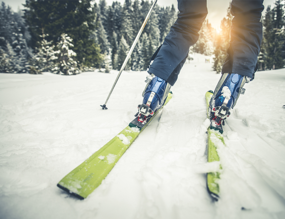 A close-up from behind of the bottom of a skier's legs as they travel down a snowy hill lined with evergreen trees.