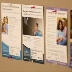 Posters advertising a variety of clinical research trials at Penn State College of Medicine are seen on a College bulletin board in summer 2016. The image shows five posters in a line, with the center one in focus and the others out-of-focus in the background.