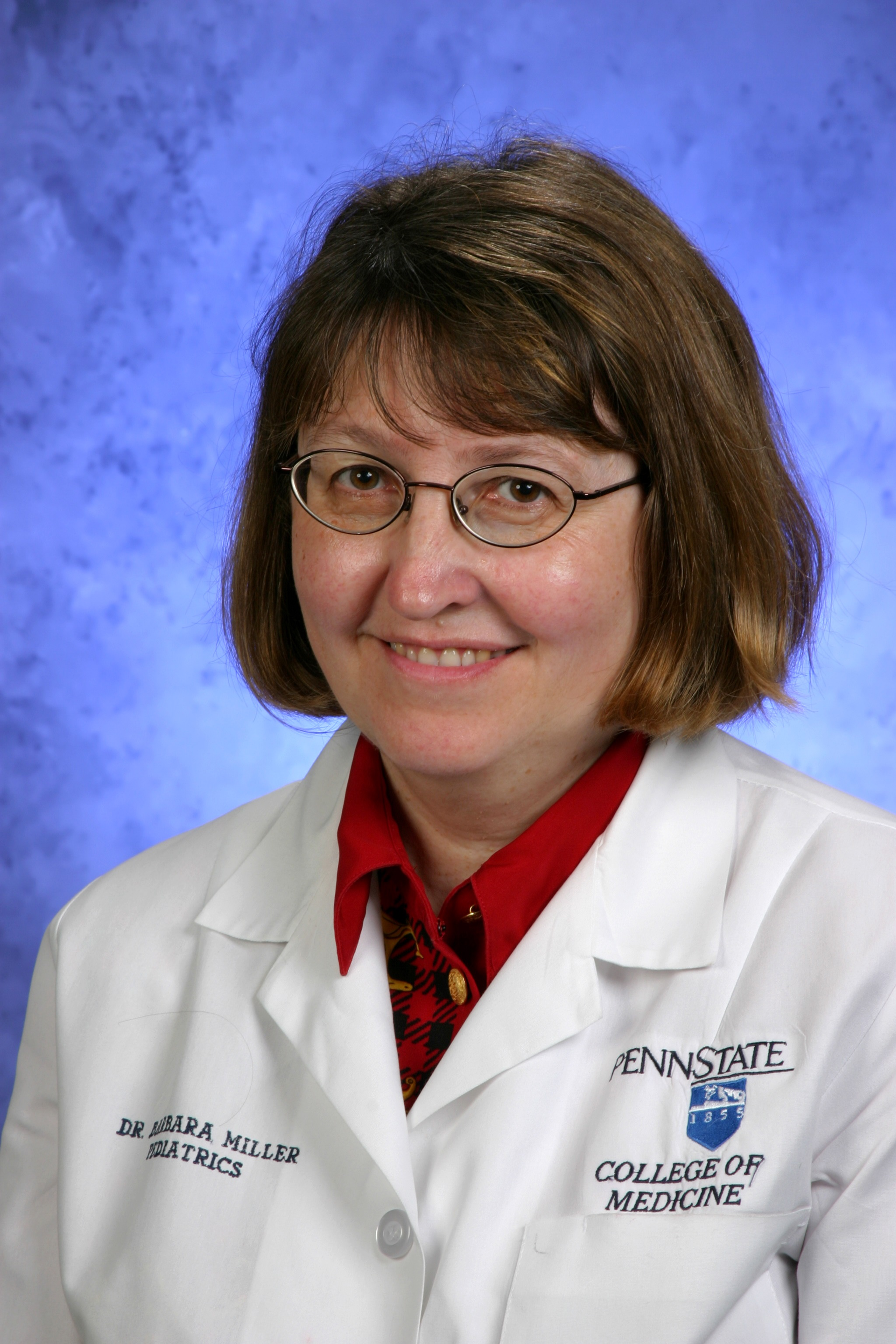 Woman with brown hair and glasses wears lab coat with Penn State College of Medicine logo.