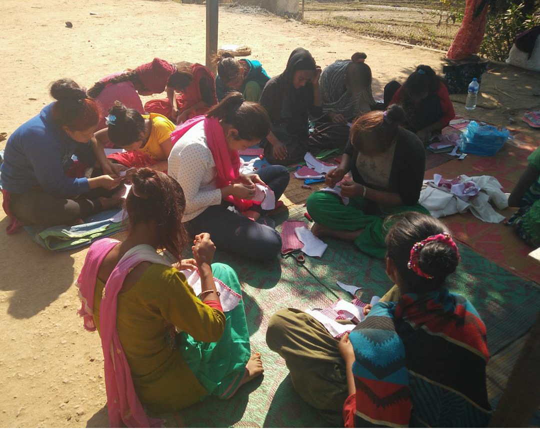 A group of 12 women and girls sit on blankets on the ground sewing small cloths. The tops of the heads are visible. Aditi Sharma, a student at Penn State College of Medicine, sits in the middle.