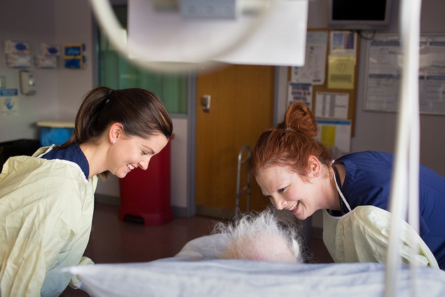 Physical Therapist Andrea Bearnger and nurse Angela Zimmerman lean over and smile at an elderly patient lying in a hospital bed. A monitor is visible above their heads.