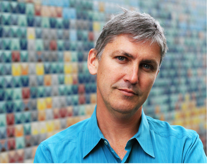 Steven Johnson is pictured wearing a collared shirt and standing in front of a wall of multicolored tiles.