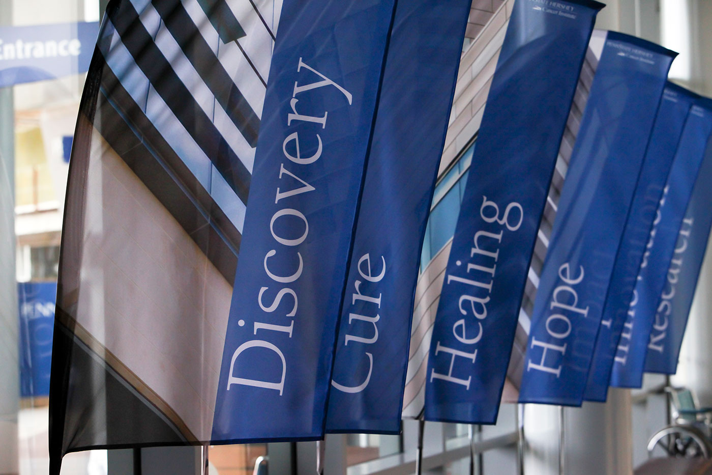 Banners inside Penn State Cancer Institute are depicted with the words Discovery, Cure, Healing and Hope visible, and other banners with unreadable text seen in the background.