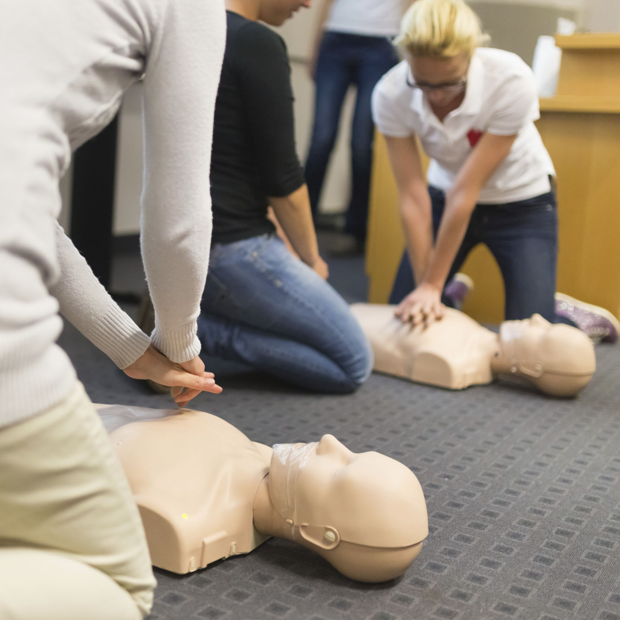 Two women practice CPR chest compressions on dummies while one person watches. The dummies lie on a carpet with a square-checked pattern. Another person stands in the background.