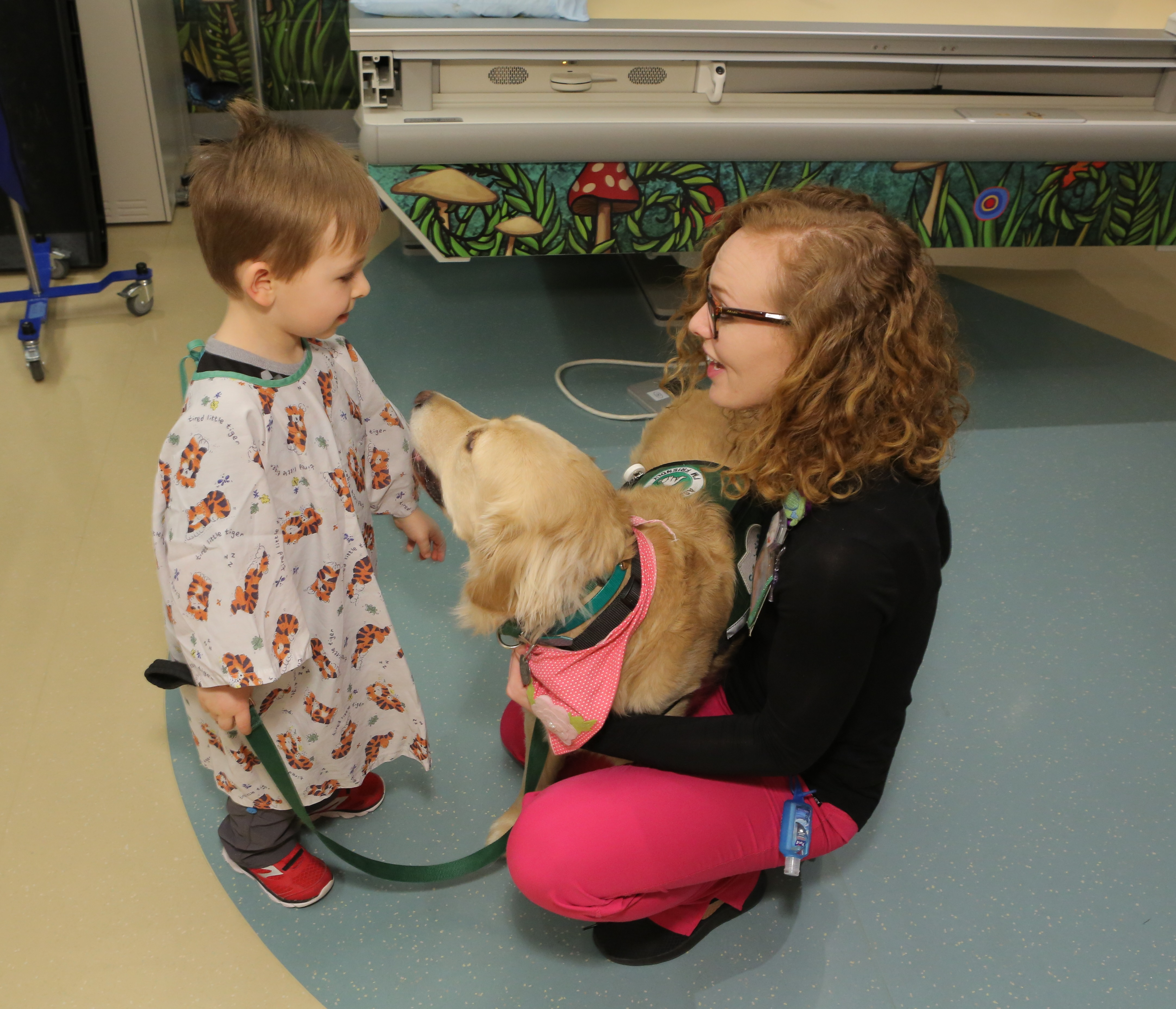 A three-year-old boy wearing a hospital smock holds a dog leash attached to a Golden Retriever. The dog looks at the boy. A young woman wearing glasses crouches down and smiles at the boy while holding the dog. Behind them is a CT scan table and a pole with wheels.
