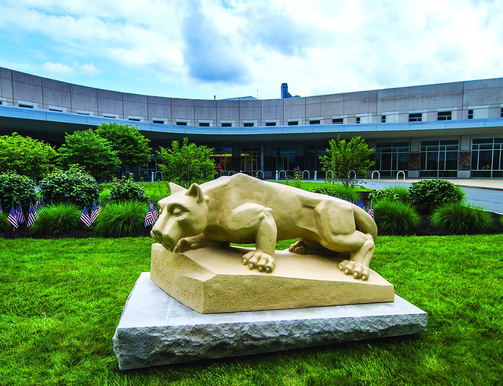A Nittany Lion statue is in the foreground; bushes are just behind it, and Penn State Health St. Joseph Regional Medical Center is in the background.