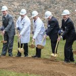 Seven people -- five in business suits, two in white physician's coats, and all wearing white helmets -- use gold shovels to dig into a pile of dirt. A stone wall is in the background.
