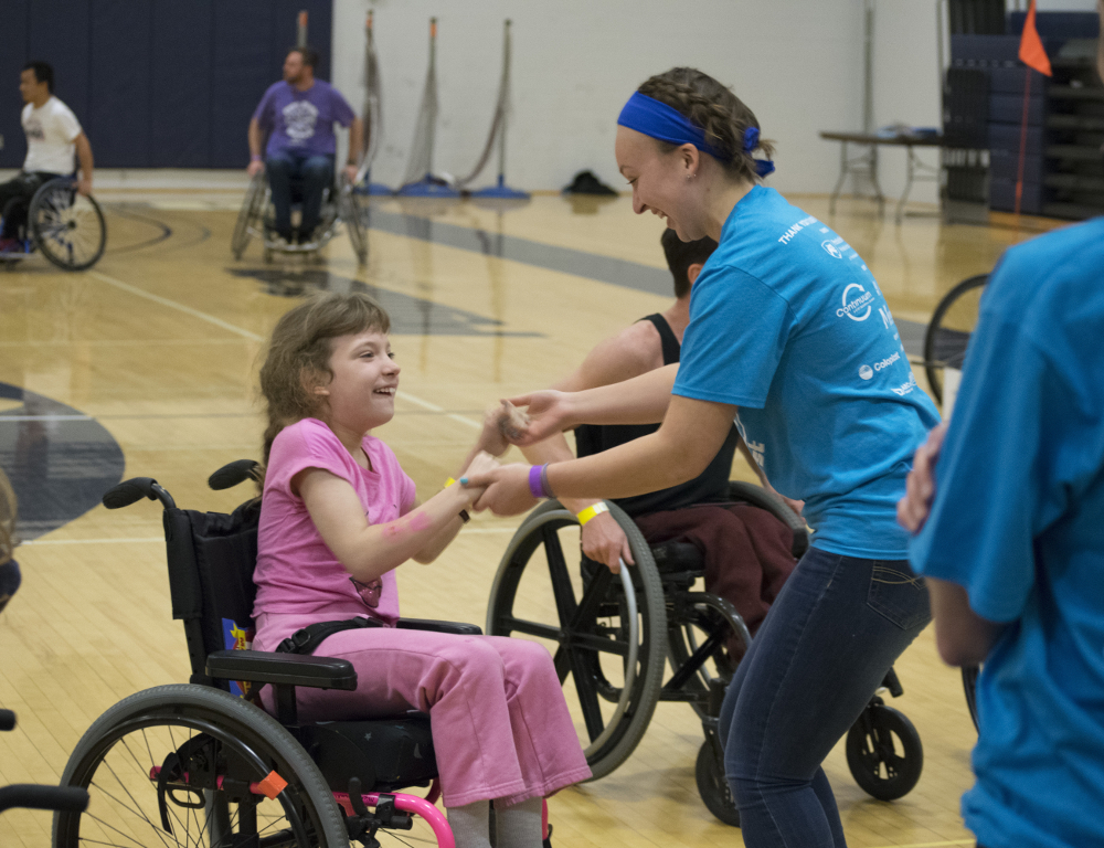 A girl in a wheelchair holds hands with a young woman volunteer as they dance. Other people in wheelchairs are seen in the background.
