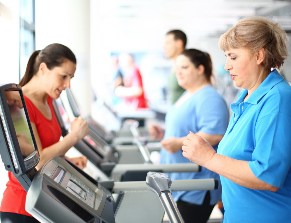 A woman in a blue shirt walks on a treadmill in the foreground. Other people are on treadmills in the background.