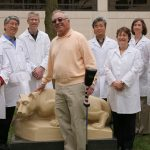 Warren Gittlen, center, holding golf club, stands in front of a statue of the Nittany Lion with seven Penn State researchers. They are outdoors. The researchers, a mix of both men and women, are wearing white lab coats.