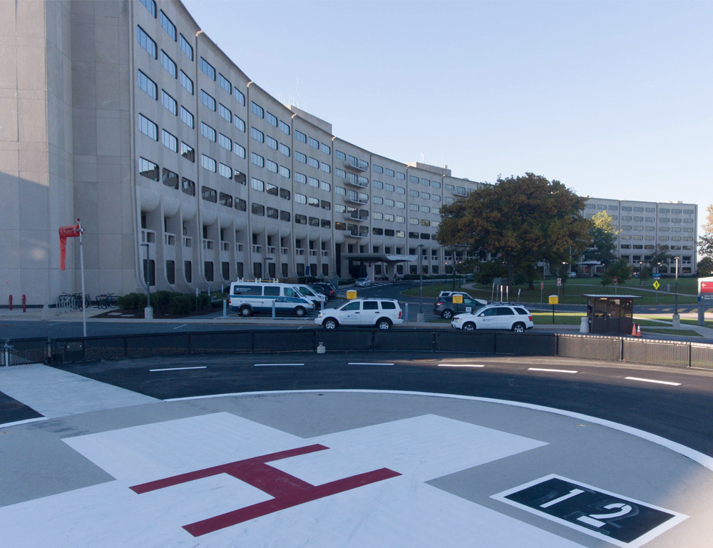 The Life Lion helipad at Hershey Medical Center is in the foreground, with a large white cross with a red