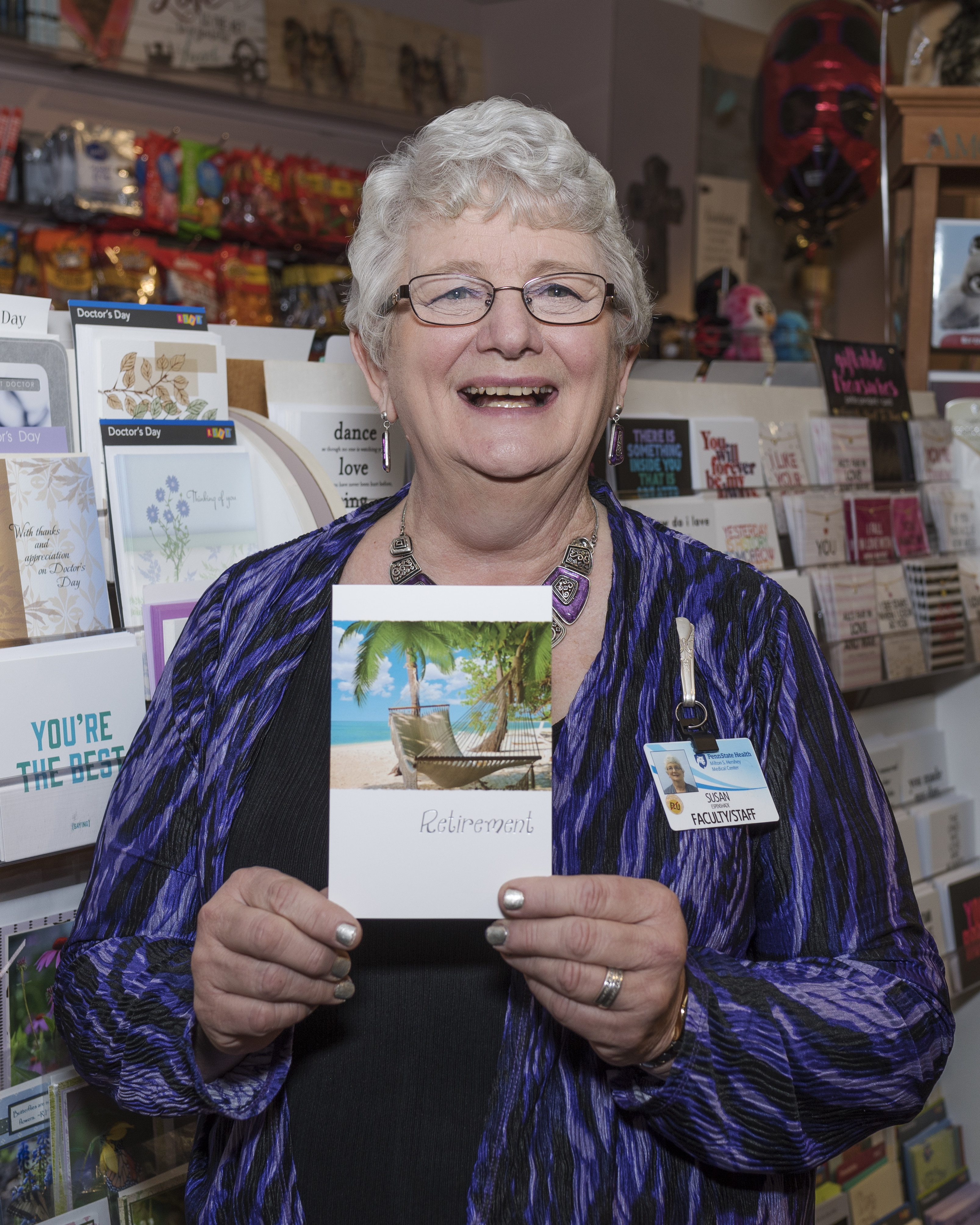 A woman holds a retirement card in the card section of a gift shop. She is smiling. She is wearing glasses.