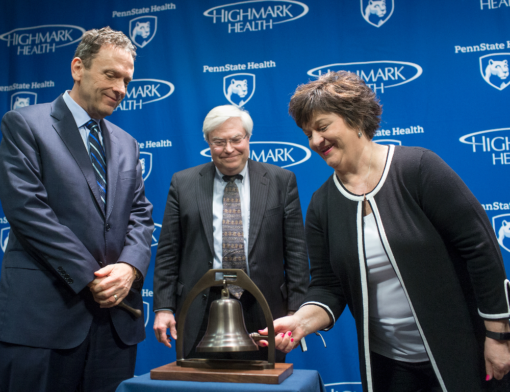 Rosemary Manbachi, a Penn State Cancer Institute patient, rings a bell symbolizing the end of an individual's cancer treatment. Looking on are David L. Holmberg, president and CEO of Highmark Health (left), and Dr. Ray Hohl, director of Penn State Cancer Institute (center). A blue backdrop contains the Highmark Health and Penn State Health logos.