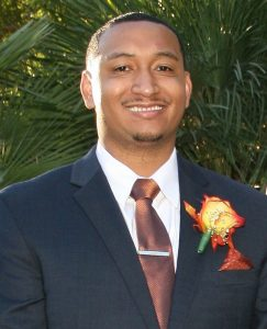 Jordan Hughey is seen in a head-and-shoulders photo, wearing a suit, tie and corsage.