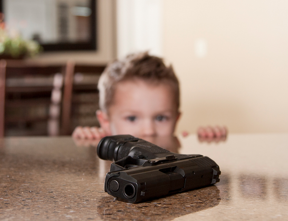 A handgun sits on a counter in the foreground. In the background, a child, slightly out of focus, peers over the counter at the gun.