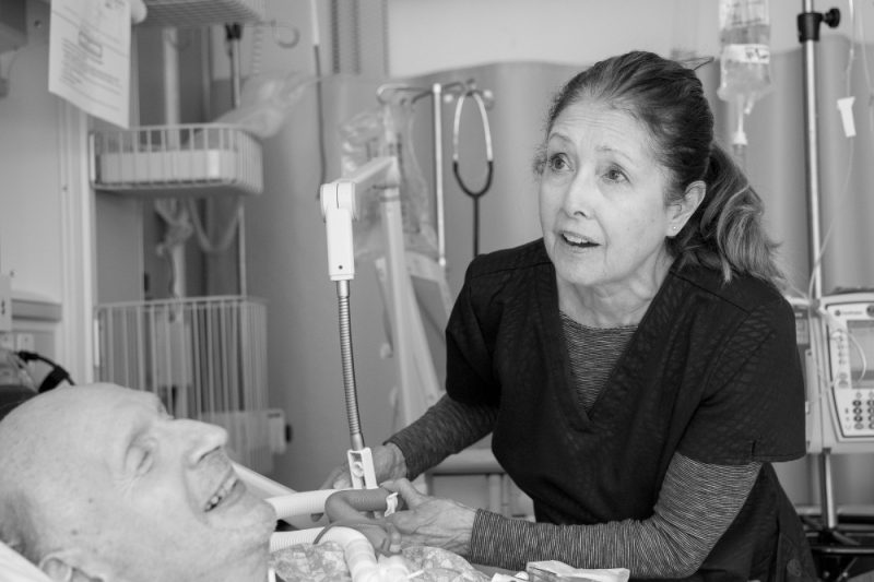 A female nurse leans over a male patient's bed while holding onto a ventilation tube. Various medical equipment is in the background.