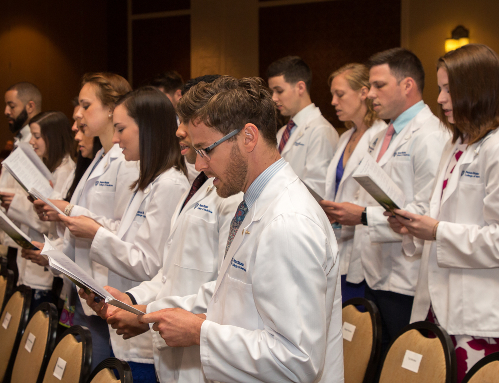 Several people in white coats stand in two rows, each looking down at a paper from which they are apparently reciting.