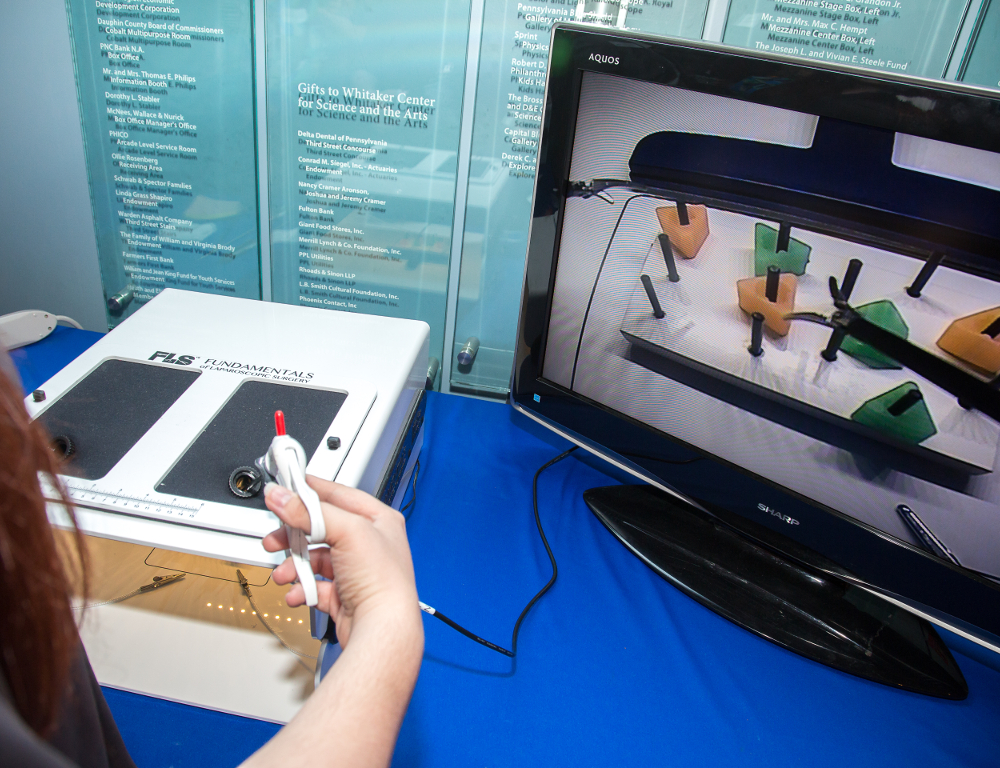 A close-up of a person's right-hand holding a device that's part of a table-top surgery simulator. A monitor is to the right of the device.