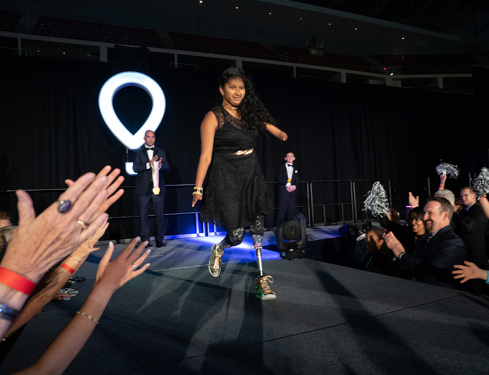 A young girl with a prosthetic leg walks on a stage as people standing around the stage applaud. The CMN (balloon) logo is in the background.