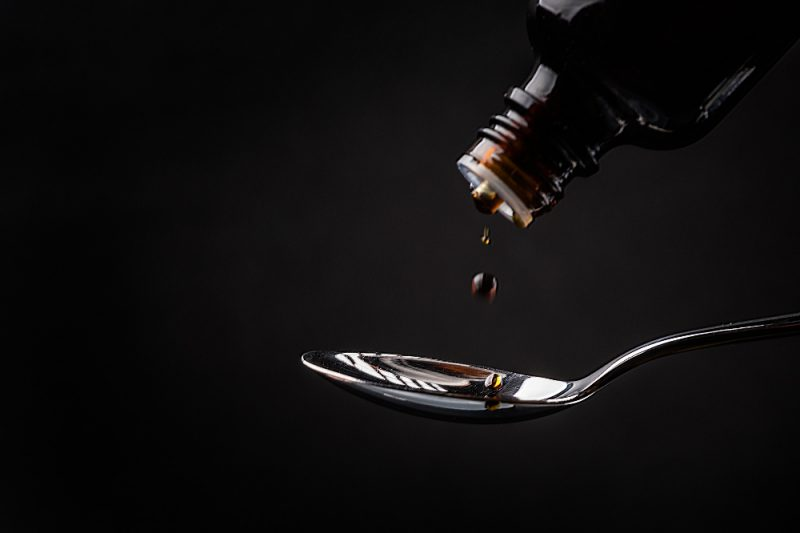 A close-up of liquid being poured out of a dark bottle onto a spoon, against a black backdrop.