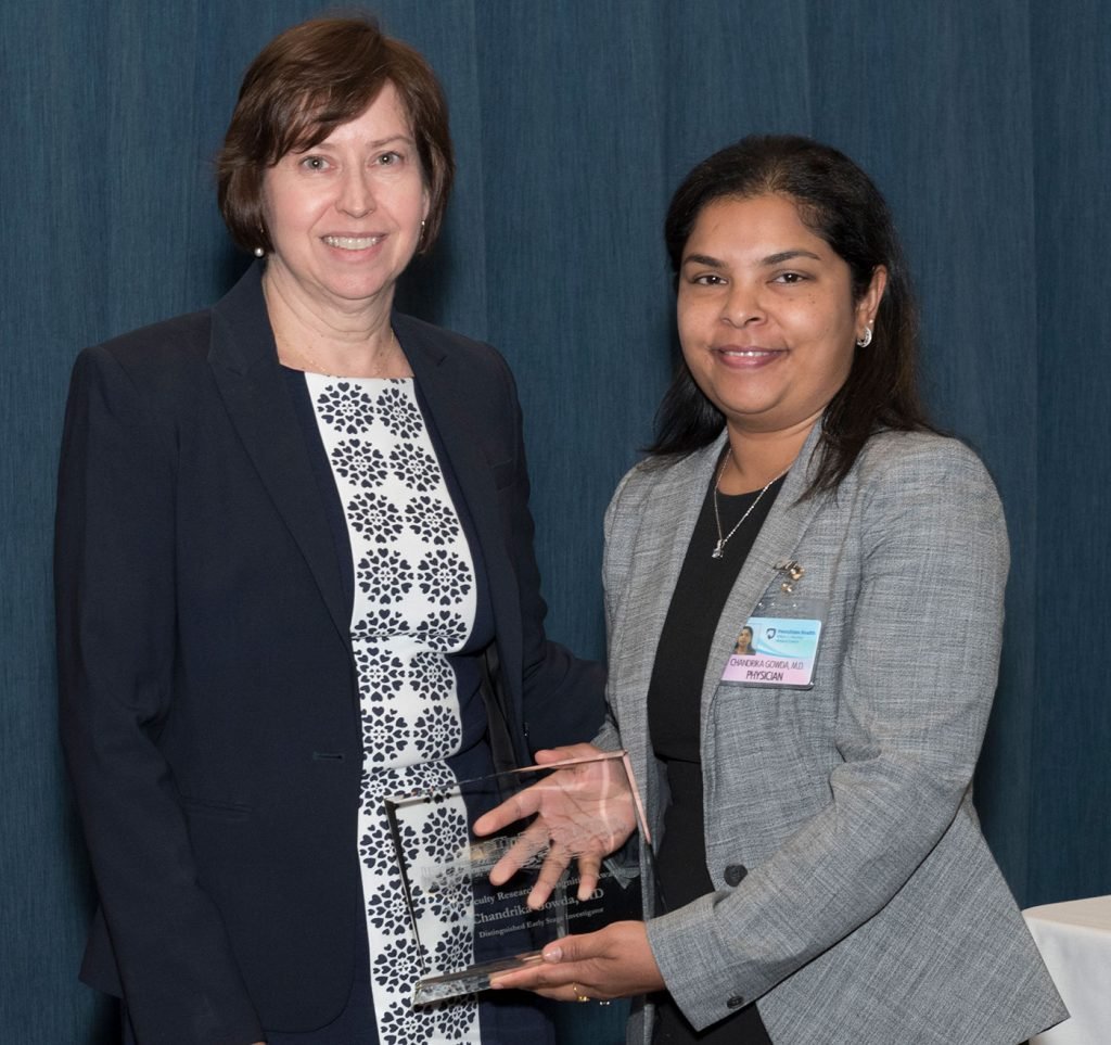 Dr. Chandrika Gowda is pictured standing with Dr. Leslie Parent after Gowda received one of two 2018 Distinguished Early Stage Investigator Awards, which she is holding.
