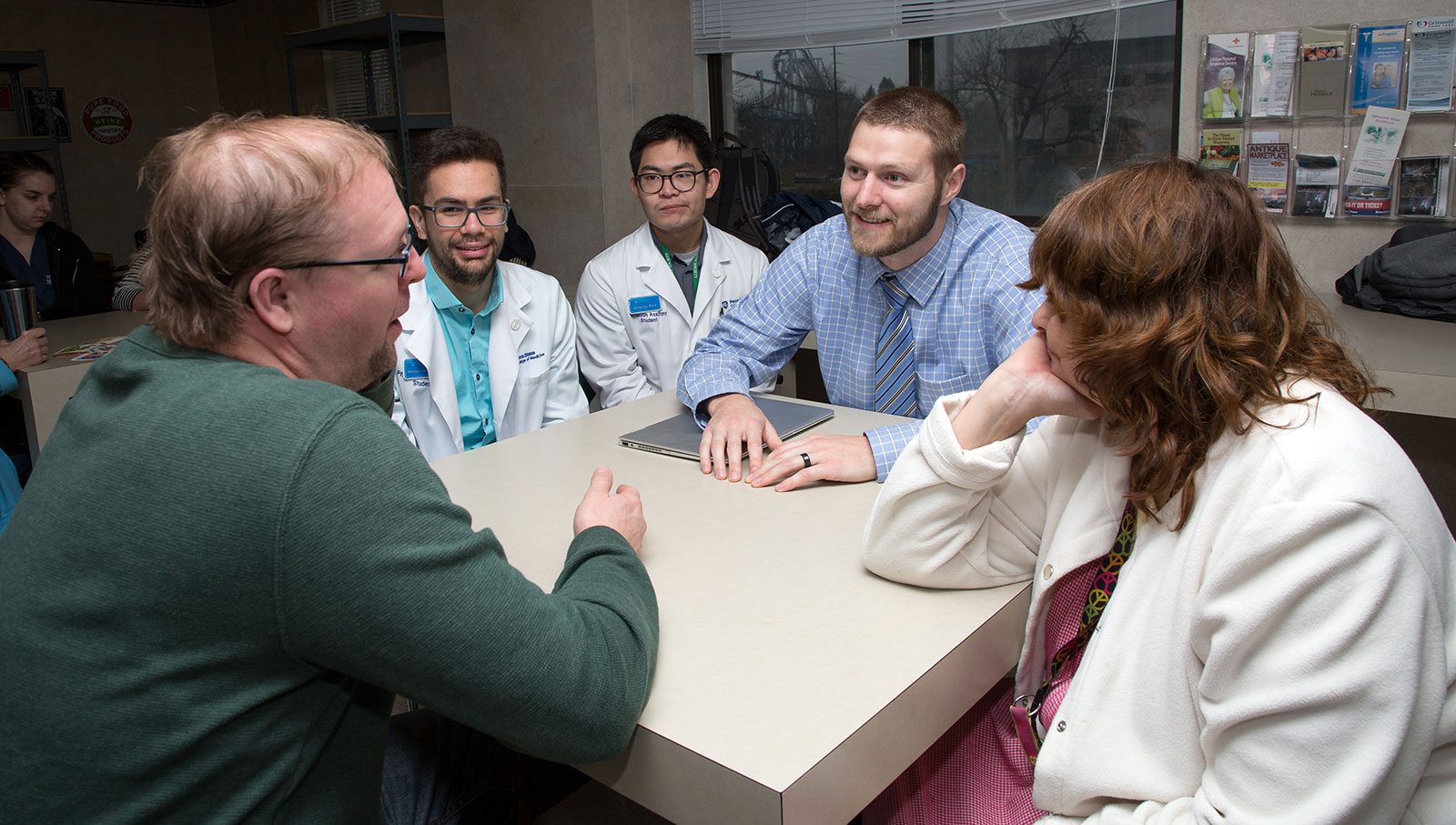 Penn State College of Medicine students work with people at Hershey Plaza Apartments as part of a health fair event. The students are pictured sitting around a square table.