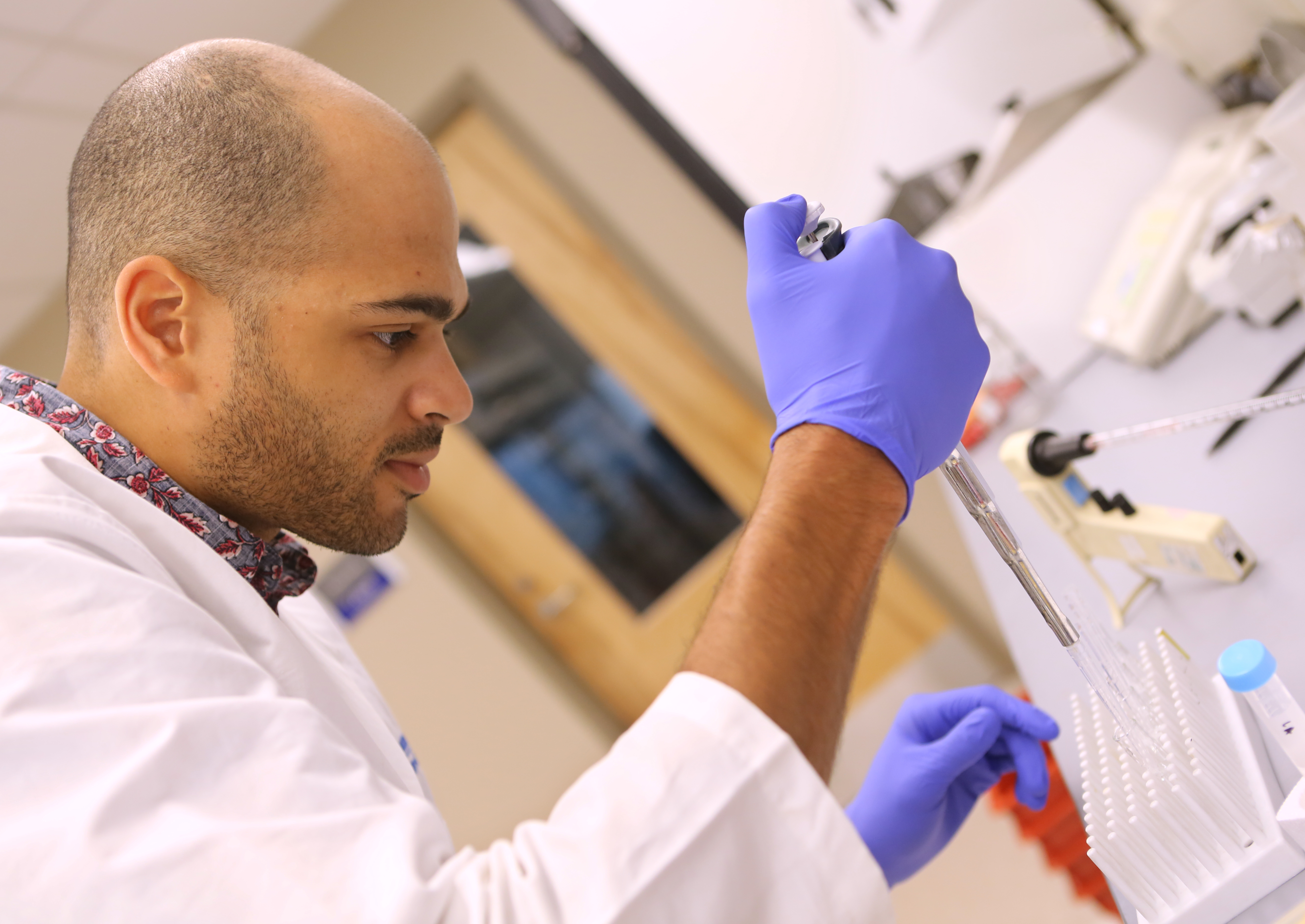A young man working in a medical research lab inserts liquid into a test tube. He is pushing a plunger with his thumb. The photo is shot at an angle. The man is wearing a lab coat and rubber gloves. Other lab equipment is on the table, and a door is behind him out of focus.