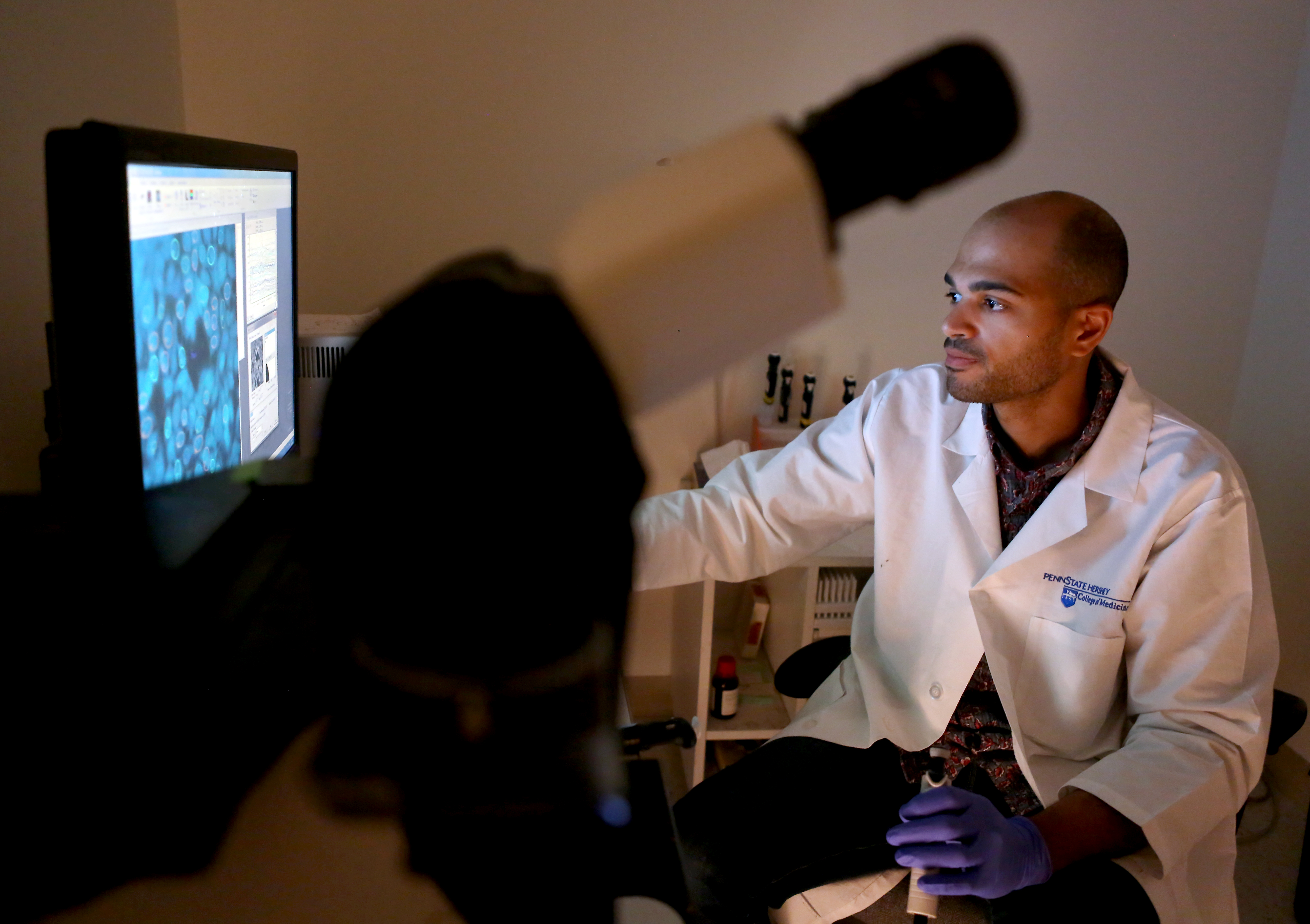 A young man wearing a Penn State College of medicine lab coat and rubber gloves examines cells on a monitor. A microscope is in the foreground. Behind him is a shelf with medical research supplies.