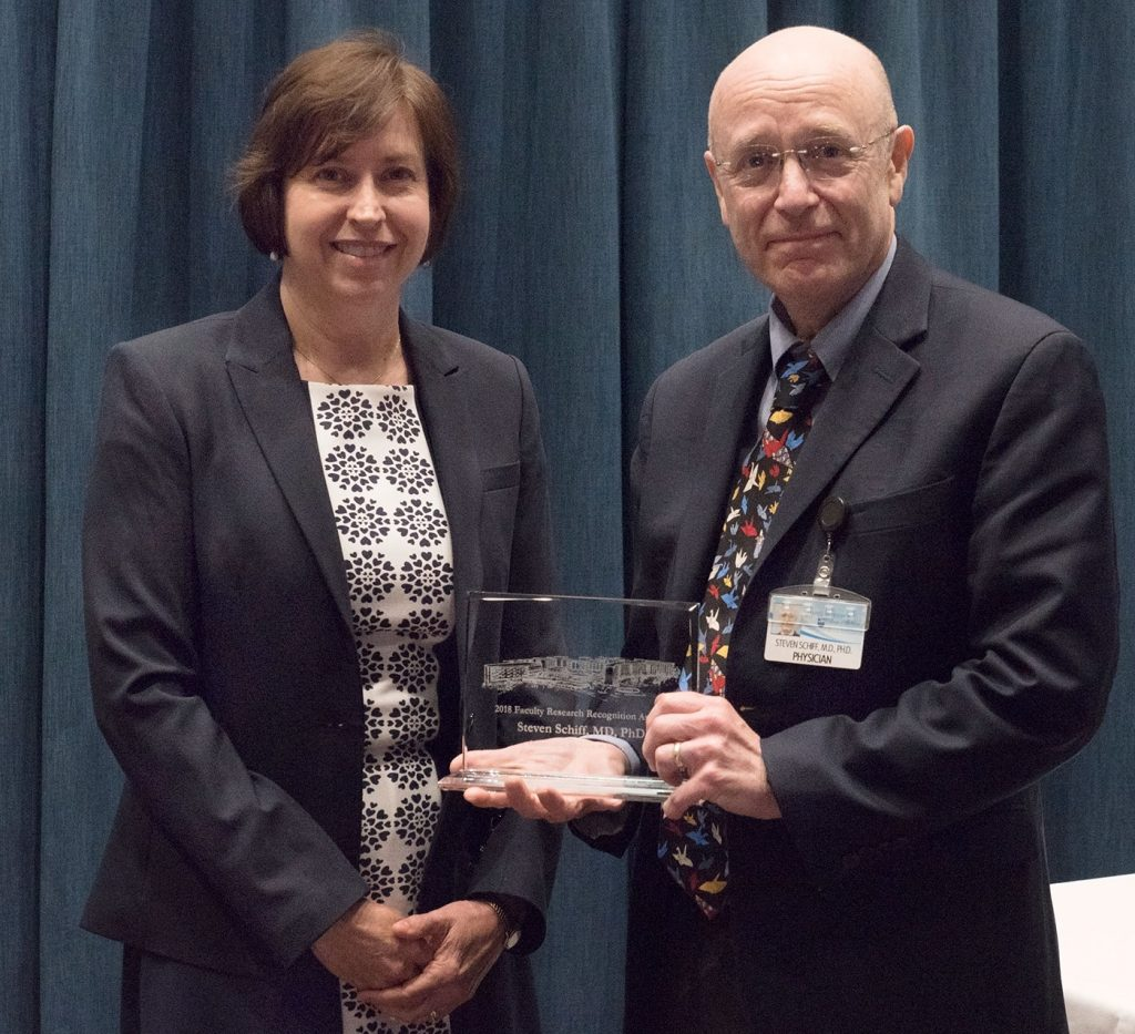 Dr. Steven Schiff is pictured standing with Dr. Leslie Parent after Schiff received one of two 2018 Outstanding Research Publication Awards, which he is holding.