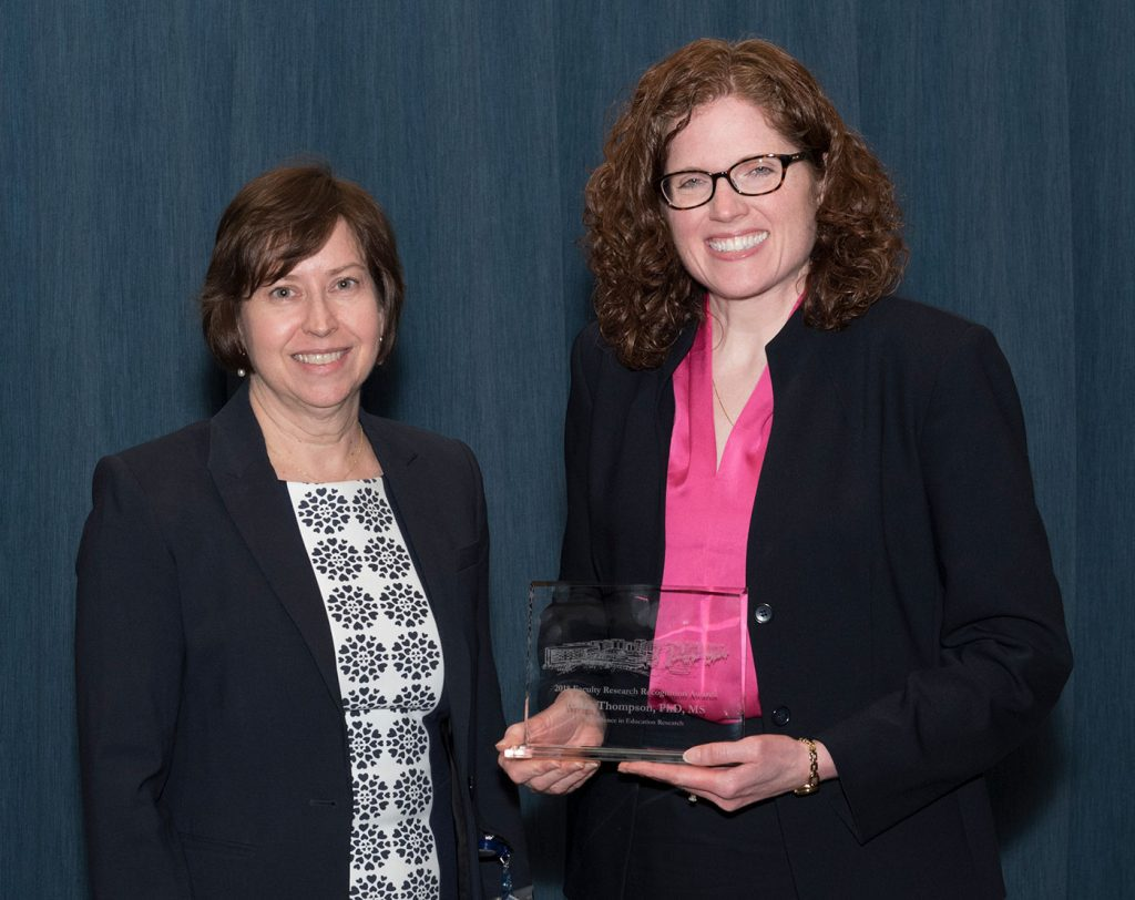 Dr. Britta Thompson is pictured standing with Dr. Leslie Parent after Thompson received the 2018 Excellence in Education Research Award, which she is holding.