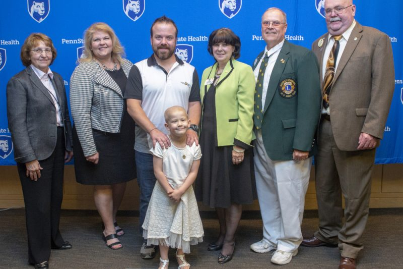 Six adults and one young girl pose for a photo. The girl is in front, smiling. The backdrop has several 'Penn State Health' logos.