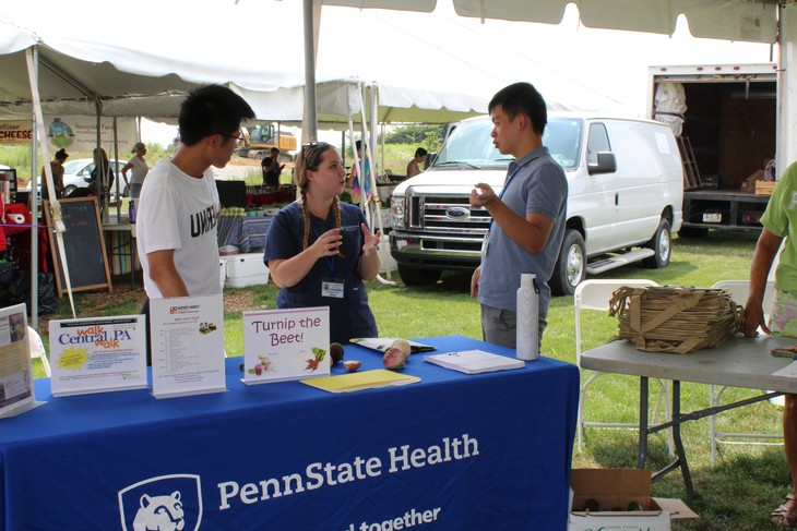 Two visiting Global Health Exchange Program students staff a table at the Farmers Market in Hershey in 2017. Three people are pictured standing behind a table in an outdoor space, with the table covered by a blue cloth with the Penn State Health logo.