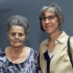 Two women stand side-by-side posing for a photo. The backdrop is a dark blue wall. A Penn State Health logo is on the wall to the left, slightly out of focus.