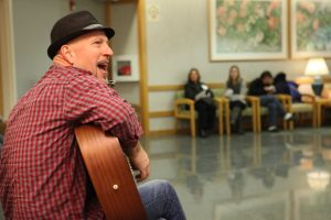Musician Steven Courtney is pictured playing a guitar and singing in a lobby at Penn State Health Milton S. Hershey Medical Center. A few people can be seen out of focus in the background, listening to the performance.