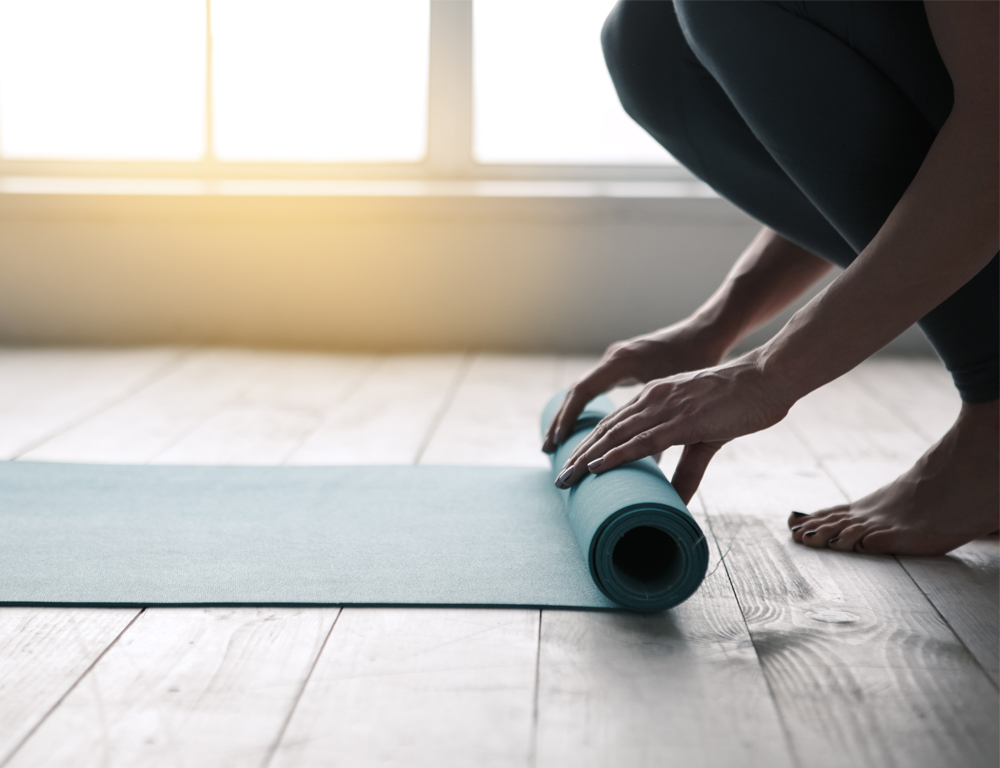 A close-up of a woman's hands as they roll up a yoga mat, which is on a hardwood floor. Windows are in the background.