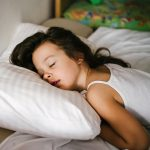 A young girl sleeps in bed, with her head on a pillow. Her head is facing the camera.
