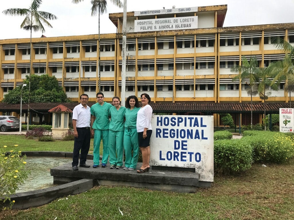 Global Health Scholars Rolfy Perez, Olivia Munizza and Ivana Marji pose with staff at the Hospital Regional de Loreto in Peru during their fourth-year trip. The four-story yellow and white hospital is flanked by palm trees and shrubs.