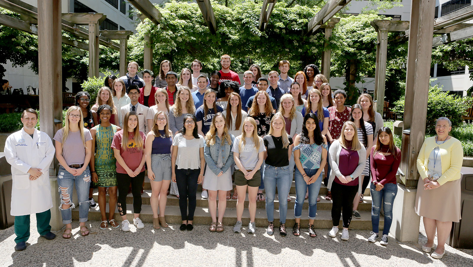 Students from the Primary Care Scholars program held at Penn State College of Medicine are seen with Dr. Andrew Lutzkanin, front left, and Diane Ferron, front right, of the Department of Family Community Medicine. The large group is pictured standing in an outdoor space under a plant-covered pergola.