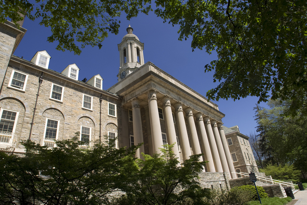Penn State's Old Main building is seen in State College, PA. The building includes a number of columns in the front and is framed by trees.