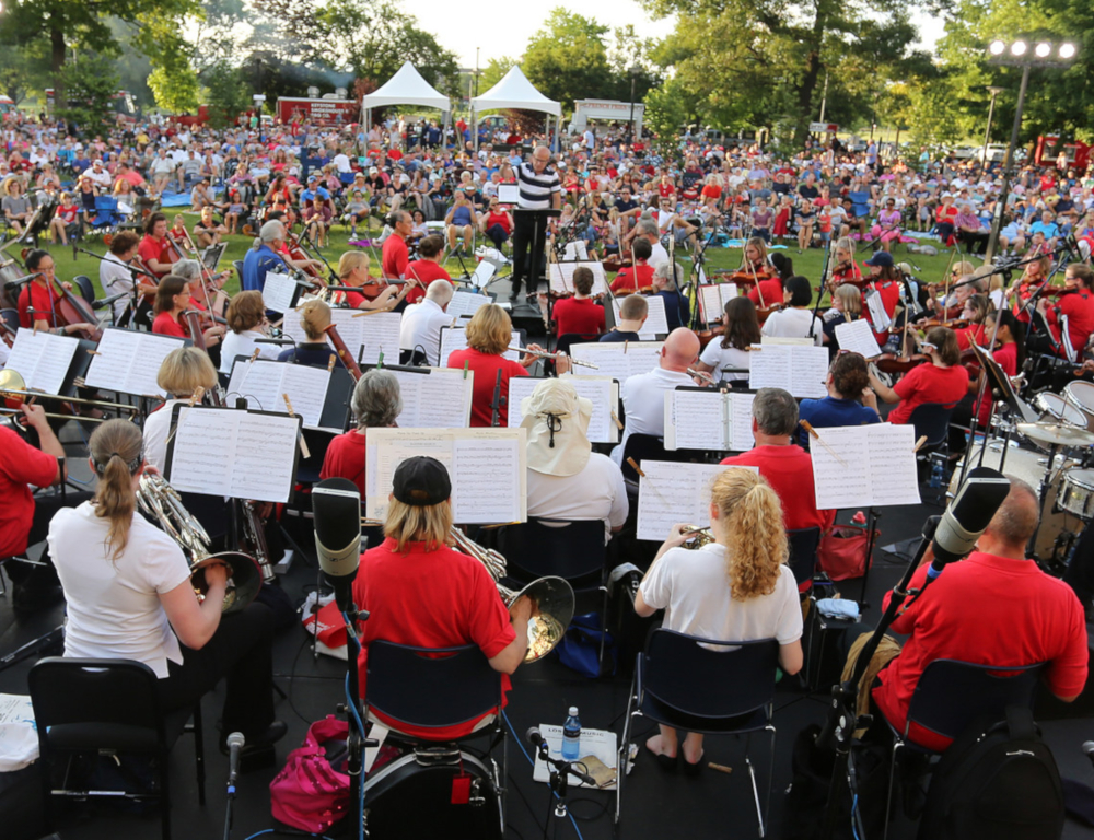 Several orchestral musicians are in the foreground, playing a range of instruments at an outdoor concert. A large audience is in the background, looking on.
