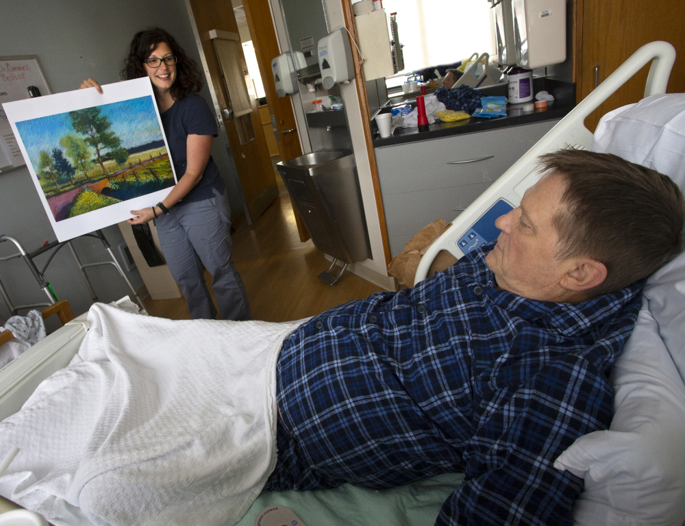 A man lays in a hospital bed. A woman stands at the foot of the bed holding a painting, showing it to him.