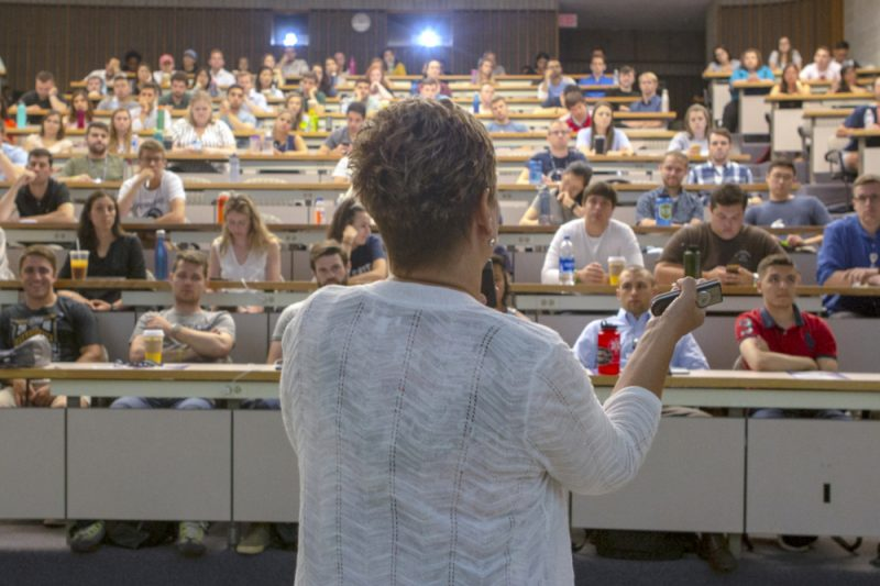 A woman in the foreground faces away from the camera, gesturing with her hands. She speaks to a crowd of people, seated in several tiered rows in a classroom.