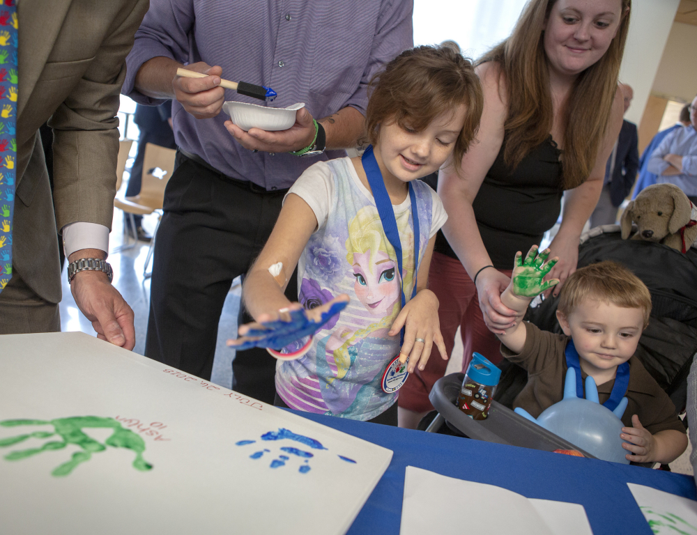 "Two young children "" a boy and a girl, have paint on each of their right hands and are preparing to place them on a white canvas, which is placed on a table. Several people stand nearby in the background."