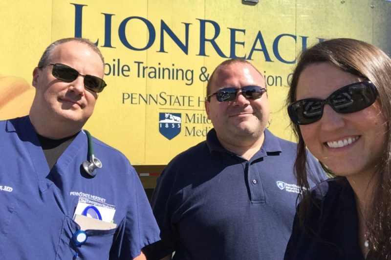"Three people – two men and one woman – pose for a photo in front of a large trailer that has the word ""LionReach"" on it as well as the Penn State Health Milton S. Hershey Medical Center logo."